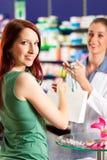 Vrouwelijke apotheker in haar apotheek met een klant Stock Afbeelding