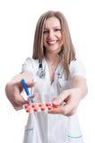 Vrouwelijke apotheker scherpe blaar van pillen die schaar met behulp van Stock Fotografie