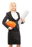 Vrouwelijke architect die in zwart kostuum een helm en een blauwdruk houden Stock Fotografie