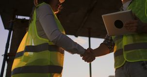 Vrouwelijke architect en bouwvakker het schudden handen Lage hoekmening, exemplaarruimte stock videobeelden