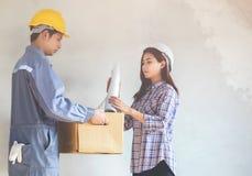 Vrouwelijke architecten die blauwdrukken met ingenieurs voor inspecti houden stock afbeeldingen