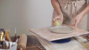 Vrouwelijke artisanaal maakt kleiplaat indient langs haar studio, die spatie roteren stock videobeelden