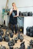 Vrouwelijke artisanaal met ceramische vazen in atelier stock foto's