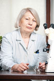 Vrouwelijke arts in bureau met microscoop royalty-vrije stock afbeelding