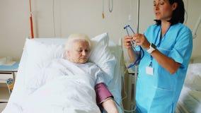 Vrouwelijke Arts Checking Blood Pressure van Patiënt stock video