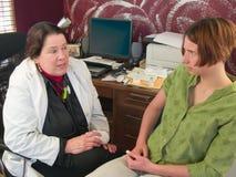 Vrouwelijke arts die aan betrokken patiënt spreekt Stock Afbeeldingen