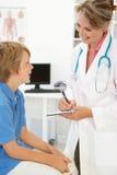 Vrouwelijke arts die aan jonge jongen spreekt Stock Foto