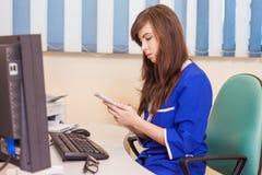 Vrouwelijke arts die aan zijn computer en met witte mobiele phon werken Stock Foto