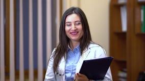 Vrouwelijke arts die camera en het glimlachen bekijken In de handen die de tablet houden stock video