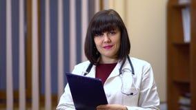 Vrouwelijke arts die camera en het glimlachen bekijken In de handen die de tablet houden stock videobeelden