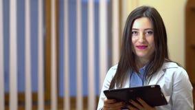 Vrouwelijke arts die camera en het glimlachen bekijken In de handen die de tablet houden stock footage