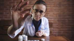 Vrouwelijke arts die capsulepillen tonen Vrouw de blaar van de artsenholding van antibiotica en het spreken aan camera geneeskund stock video