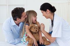 Vrouwelijke arts die de keel van haar patiënt controleert Royalty-vrije Stock Foto's