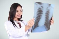 Vrouwelijke arts die die en röntgenstraal glimlachen lezen, op groene backg wordt geïsoleerd Royalty-vrije Stock Foto's