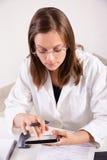 Vrouwelijke arts die digitale tablet in bureau gebruiken Stock Foto's