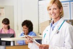 Vrouwelijke Arts die Digitale Tablet gebruikt bij de Post van Verpleegsters royalty-vrije stock afbeeldingen