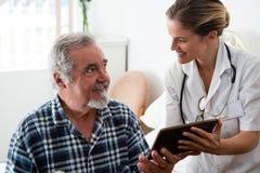 Vrouwelijke arts die digitale tablet tonen aan de mens in pensioneringshuis Stock Fotografie