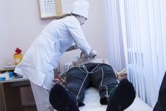 Vrouwelijke arts die ECG-elektrocardiogram van patiënt bij in het ziekenhuis analyseren Royalty-vrije Stock Fotografie