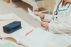 Vrouwelijke arts die een leeg blad van document met een medisch voorschrift houden tijdens de controle royalty-vrije stock fotografie