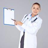 Vrouwelijke arts die een leeg klembord tonen Stock Foto's
