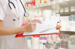 Vrouwelijke arts die een medisch voorschrift schrijven Stock Fotografie