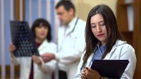 Vrouwelijke arts die een omslag in zijn handen houden Op de achtergrond, controleerden de artsen de röntgenstralen stock video