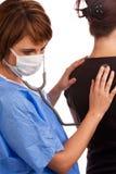 Vrouwelijke arts die een patiënt onderzoekt Stock Afbeeldingen
