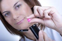 Vrouwelijke arts die een pil houdt Stock Afbeeldingen