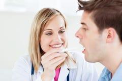 Vrouwelijke arts die een speekselsteekproef neemt Royalty-vrije Stock Afbeeldingen