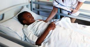 Vrouwelijke arts die een ziek meisje onderzoeken stock videobeelden