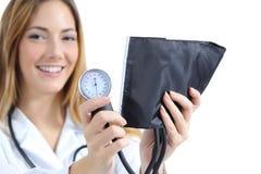 Vrouwelijke arts die en een sphygmomanometer houden tonen royalty-vrije stock foto's