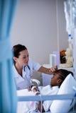 Vrouwelijke arts die geduldige koorts in afdeling controleren Royalty-vrije Stock Afbeelding