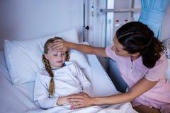 Vrouwelijke arts die geduldige koorts in afdeling controleren Stock Afbeelding