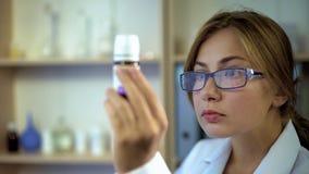 Vrouwelijke arts die geneeskundeingrediënten bestuderen, die bij etiket van pillencontainer staren stock foto's