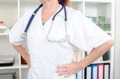Vrouwelijke arts die haar handen op haar heupen houden royalty-vrije stock foto