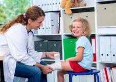 Vrouwelijke arts die het been van a van meisje verbinden Royalty-vrije Stock Fotografie