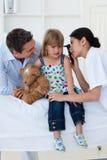 Vrouwelijke arts die het glimlachen de oren van het meisje controleert Royalty-vrije Stock Foto