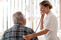 Vrouwelijke arts die hogere patiënt met stethoscoop onderzoeken Royalty-vrije Stock Afbeeldingen