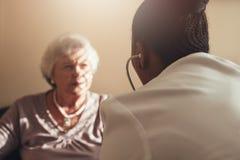Vrouwelijke arts die hogere patiënt onderzoekt Royalty-vrije Stock Foto
