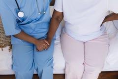 Vrouwelijke arts die hogere vrouw in slaapkamer thuis troosten royalty-vrije stock fotografie