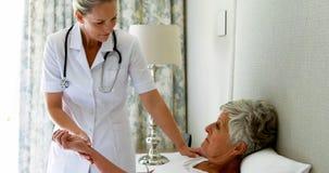 Vrouwelijke arts die hogere vrouwenimpuls controleren tijdens controle in slaapkamer stock footage
