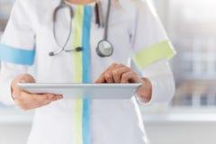 Vrouwelijke arts die ipad bij het werk in het ziekenhuis gebruiken Stock Afbeelding