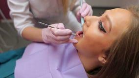 Vrouwelijke arts die jonge meisjes` s tanden in het tandbureau onderzoeken stock footage