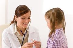 Vrouwelijke arts die kind met stethoscoop onderzoekt royalty-vrije stock afbeelding