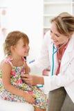 Vrouwelijke arts die kind onderzoekt Stock Afbeelding