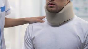 Vrouwelijke arts die mannelijke geduldige schuim cervicale kraag, halsverwondingen, spanning toepassen stock video