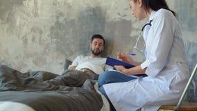 Vrouwelijke arts die mannelijke patiënt thuis bezoeken stock footage