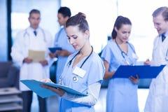 Vrouwelijke arts die medisch rapport controleren Royalty-vrije Stock Foto