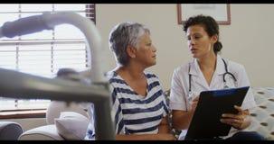 Vrouwelijke arts die met hogere vrouw in woonkamer 4k interactie aangaan stock footage
