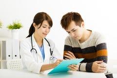 Vrouwelijke arts die met patiënt in bureau spreken stock foto's